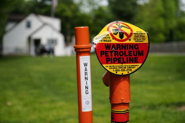 A warning sign is posted along the path of the Colonial Pipeline in Garnet Valley, Pa., Monday, May 10, 2021. (AP Photo/Matt Rourke)