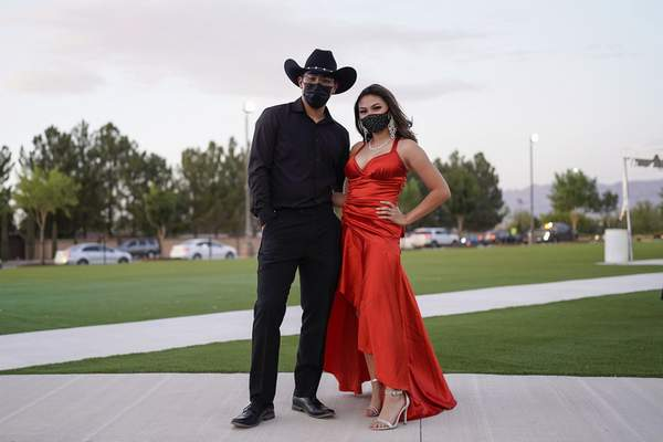 Sean de la Luz, 18, and Nalanie Miranda, 18, wear face masks for their prom at the Grace Gardens Event Center in El Paso, Texas on Friday, May 7, 2021. (AP Photo/Paul Ratje)