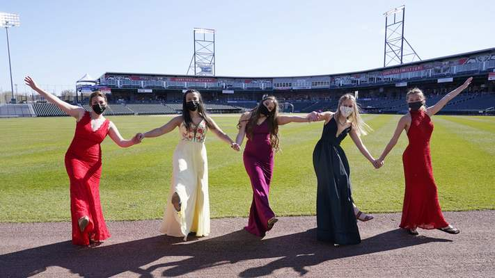 While wearing their prom gowns, students pose for a photograph in the outfield at the New Hampshire Fisher Cats minor league baseball stadium in Manchester, N.H., on Monday, April 26, 2021. (AP Photo/Charles Krupa)