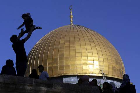 APTOPIX Israel Palestinians A girl is tossed into the air as people gather for Eid al-Fitr prayers at the Dome of the Rock Mosque in the Al-Aqsa Mosque compound in the Old City of Jerusalem, Thursday, May 13, 2021. (AP Photo/Mahmoud Illean) (Mahmoud Illean STF)