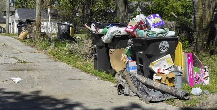 Michelle Davies | The Journal Gazette Garbage overflows containers in the alley behind Zollars Avenue.