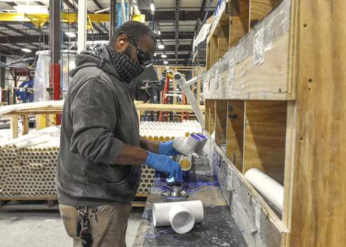 Photos by Michelle Davies | The Journal Gazette Jonathan Mathus, with at Master Spas, preassembles plumbing parts to help streamline the making of a swim spa.