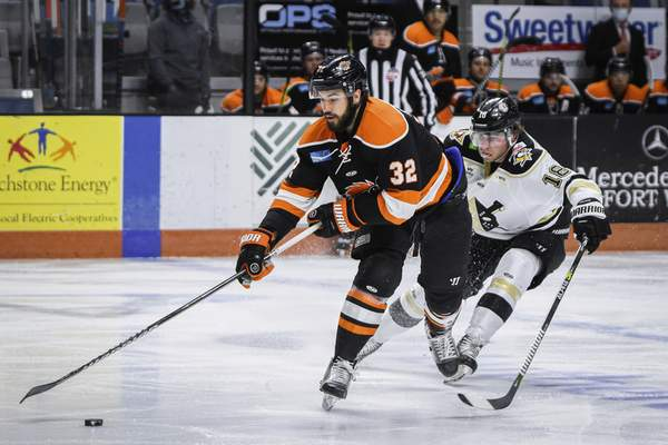 Mike Moore   The Journal Gazette Komets forward Morgan Adams-Moisan keeps the puck away from Nailers forward Brady Tomlak in the first period at Memorial Coliseum on Friday.
