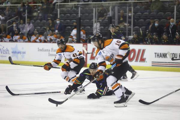 Whiteshark Photography  Komets defenseman Nick Boka, bottom, looks to make a pass to forward Zach Pochiro, top, as the Indy Fuel's Diego Cuglietta defends from the ice Friday at Indiana Farmers Coliseum in Indianapolis.