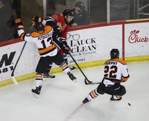 Whiteshark Photography  The Komets' Anthony Petruzzelli, left, and Matt Murphy, right, try to force a turnover Monday night against the Indy Fuel's Josh Dickinson at Indianapolis.