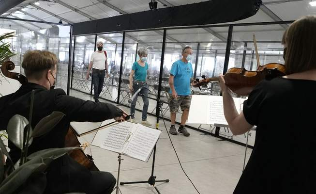 Christoph Bunzendahl on cello, left, and Annick Sauvanaud on violin, right, perform in the waiting room at the Antwerp Vaccine Village in Antwerp, Belgium, on Monday, May 31, 2021. (AP Photo/Virginia Mayo)
