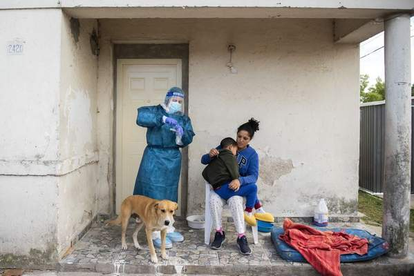 FILE - In this March 18, 2021 file photo, a healthcare worker prepares to test a child for COVID-19, on the outskirts of Montevideo, Uruguay. (AP Photo/Matilde Campodonico, File)