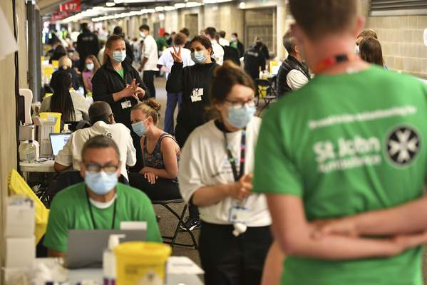 People queue up to receive a coronavirus vaccination at a surge vaccine operation set up at Twickenham rugby stadium, south-west London, Monday May 31, 2021. (Dominic Lipinski/PA via AP)