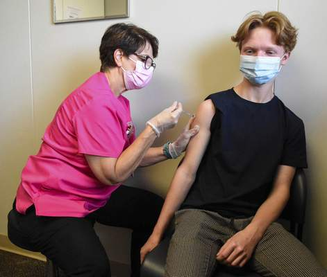 Michelle Davies | The Journal Gazette Registered nurse Jeri Hillabrand gives a COVID-19 vaccination shot to Aidan Webb, 16, of Spencerville, on Tuesday  at Super Shot on Hobson Road.