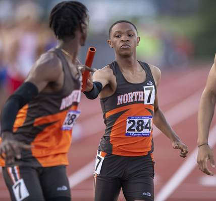 A'Careon James (284), Fort Wayne Northrop, hands the baton off to teammate Jemel Kerlegrand (285), while competing in the Boys 4x400 Relay during the 117th Annual IHSAA Boys' State Track and Field Finals at Ben Davis High School, Friday, June 4, 2021. (Doug McSchooler/for Journal-Gazette)