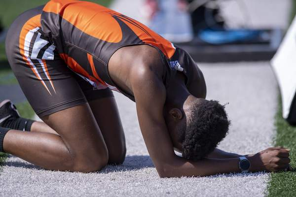 Chryzor Baltazard (282), Fort Wayne Northrop, collapses next to the track after competing in the Boys 4x800 Meter Relay during the 117th Annual IHSAA Boys' State Track and Field Finals at Ben Davis High School, Friday, June 4, 2021. (Doug McSchooler/for Journal-Gazette)