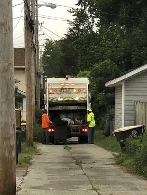 Katie Fyfe | The Journal Gazette Red River Waste Solutions employees collect trash along North Anthony Boulevard recently.