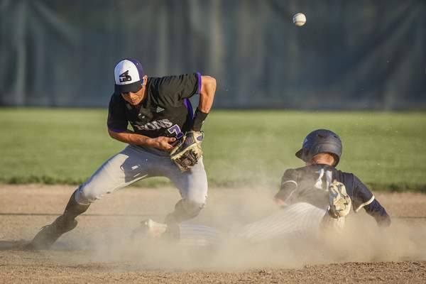 Mike Moore | The Journal Gazette Leo second baseman Braden Hicks misses the throw as Norwell senior Eli Riley slides into the bag in the first inning of the regional championship at Bellmont High School on Saturday.