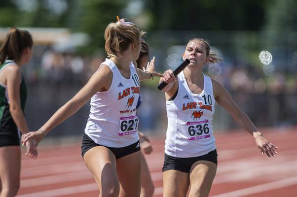 Warsaw's Ava Knight hands the baton to her teammate Adrea Beckham in 4X800 meter relay at the 2021 IHSAA Girls State Track Meet on June 5, 2021 at Ben Davis High School in Indianapolis, IN. (Credit Image: Chad Williams)