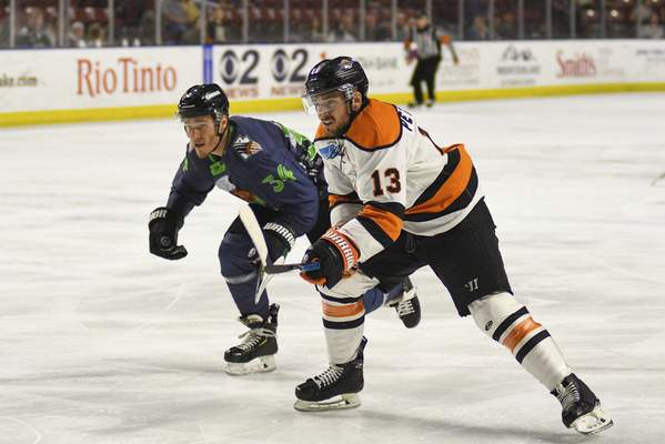 Utah Grizzlies Photography  Komets forward Anthony Petruzzelli, right, races for the puck with the Utah Grizzlies' Brandon Fehd on Saturday in West Valley City, Utah.