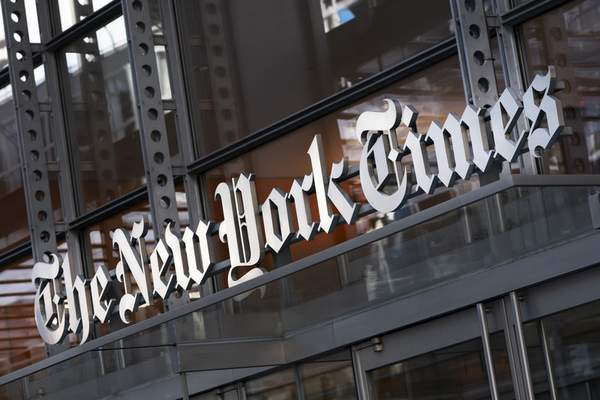 FILE - In this Thursday, May 6, 2021 file photo, a sign for The New York Times hangs above the entrance to its building, in New York. (AP Photo/Mark Lennihan, File)