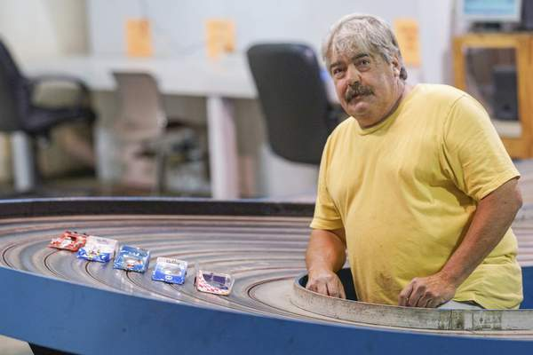 Photos by Mike Moore | The Journal Gazette Mike Holley, who started racing slot cars in 1967, poses with his king slot car track, one of the few in the state.