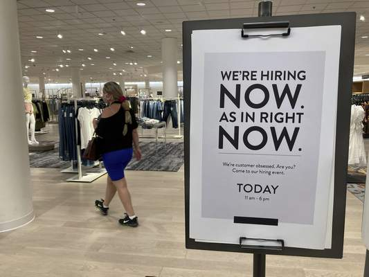 A customer walks behind a sign at a Nordstrom store seeking employees, Friday, May 21, 2021, in Coral Gables, Fla. (AP Photo/Marta Lavandier)
