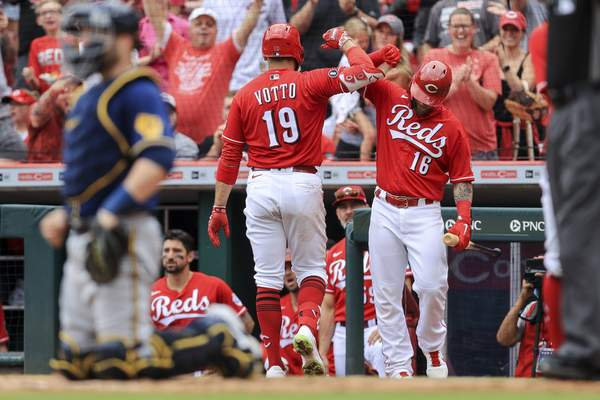 Cincinnati Reds' Joey Votto (19) celebrates hitting a solo home run with Tucker Barnhart during the second inning of a baseball game against the Milwaukee Brewers in Cincinnati, Thursday, June 10, 2021. (AP Photo/Aaron Doster)