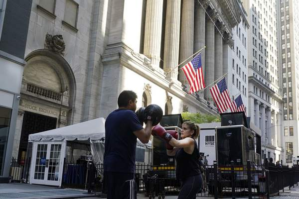 A woman and her trainer workout outside the New York Stock Exchange, Monday, June 7, 2021. (AP Photo/Richard Drew)
