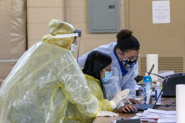 FILE: Medical workers with OptumServe Health Services prepare a COVID-19 test sample from a patient inside the National Guard Armory in La Porte, Ind. on Wednesday, May 6, 2020. (Ted Yoakum/The News-Dispatch via AP)