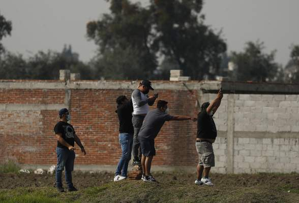 Courious onlookers try to take photos of a water filled sinkhole in Zacatapec, on the outskirts of Puebla, Mexico, Wednesday, June 9, 2021. The massive water-filled sinkhole continues swallowing farmers' fields in the central Mexican state of Puebla. (AP Photo/Fernando Llano)