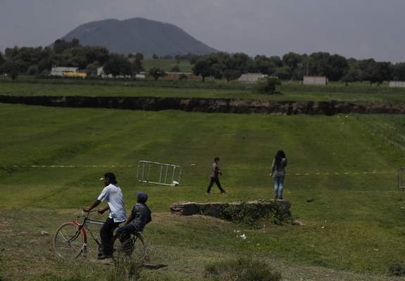 Peeple walk near a water filled sinkhole in Zacatapec, on the outskirts of Puebla, Mexico, Wednesday, June 9, 2021. The massive water-filled sinkhole continues swallowing farmers' fields in the central Mexican state of Puebla. Authorities say an underground river is responsible. (AP Photo/Fernando Llano)