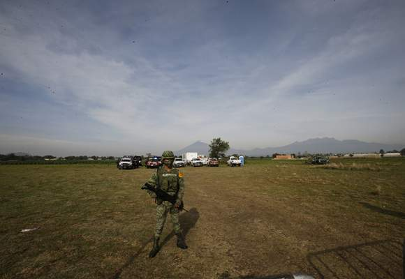 A Mexican soldier stands on guard inside a security perimeter around a water filled sinkhole in Zacatapec, on the outskirts of Puebla, Mexico,Wednesday, June 9, 2021. (AP Photo/Fernando Llano)