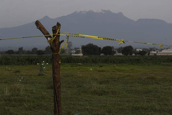 With the Iztaccíhuatl volcano in the background, security tape bars access in the perimeter around a water filled sinkhole in Zacatapec, on the outskirts of Puebla, Mexico, Wednesday, June 9, 2021. (AP Photo/Fernando Llano)