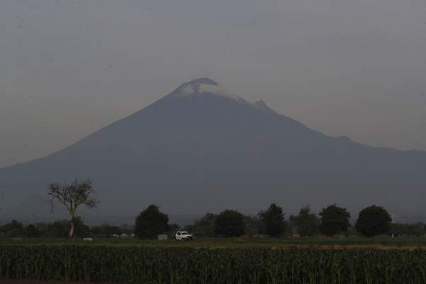 With the Popocatepetl volcano on the background, security personnel patrol the perimiter around a water filled sinkhole in Zacatapec, on the outskirts of Puebla, Mexico, Wednesday, June 9, 2021. (AP Photo/Fernando Llano)