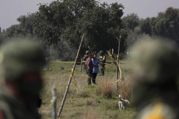 Onlookers and soldiers stand outside the safety perimeter of a water filled sinkhole in Zacatapec, on the outskirts of Puebla, Mexico, Wednesday, June 9, 2021. (AP Photo/Fernando Llano)