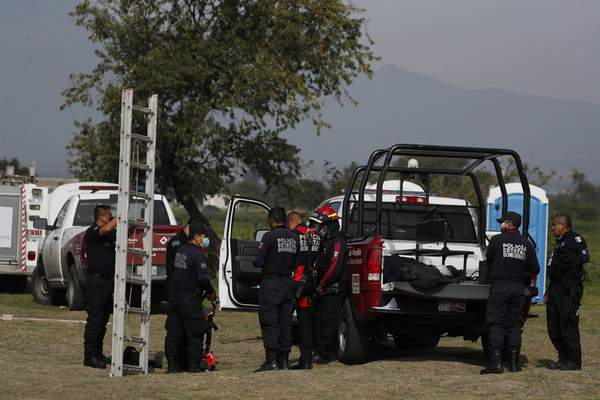 Mexican fire fighters prepare for a routine inspection of a water filled sinkhole in Zacatapec, on the outskirts of Puebla, Mexico, Wednesday, June 9, 2021. (AP Photo/Fernando Llano)