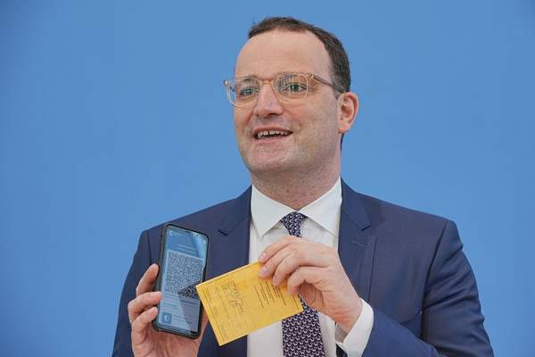 Jens Spahn (CDU), Federal Minister of Health, shows the Corona Warn app with a sample digital vaccination certificate as well as his own old vaccination certificate at the regular press conference on the Corona situation in Berlin, Germany, Thursday, June 10, 2021. (Michael Kappeler/dpa via AP)