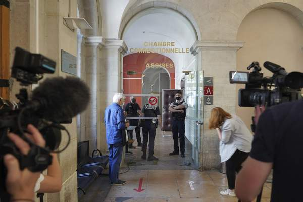 Reporters wait outside the courtroom as the 28-year-old man who slapped French President Emmanuel Macron is tried, facing possible jail time and a fine if found guilty of assaulting a public official, Thursday, June 10, 2021 in Valence, central France. (AP Photo/Laurent Cirpriani)