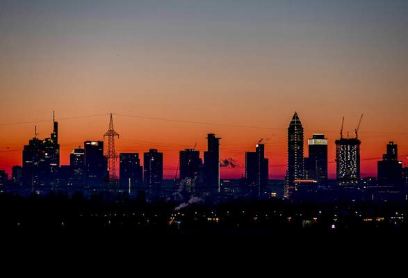 FILE - In this Feb.14, 2021 file photo the sun is about to rise behind the buildings of the banking district in Frankfurt, Germany. (AP Photo/Michael Probst, file)