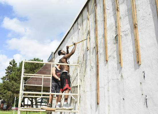 Katie Fyfe | The Journal Gazette Earl Foster, right, and Lucas Steury work on the side of a building along Wells Street on Thursday.