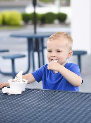 Katie Fyfe | The Journal Gazette After getting a haircut, Sullivan Jacks, 2, is rewarded with a cup of ice cream Thursday  at Zesto  off St. Joe Center Road.