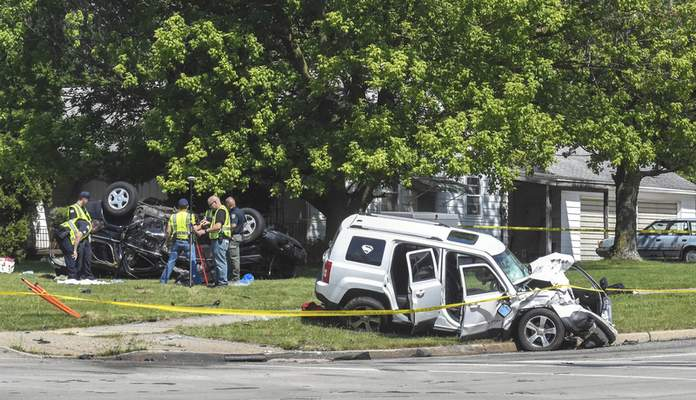 Michelle Davies | The Journal Gazette Police and emergency workers examine the scene of a crash Saturday morning at East State Boulevard and Reed Road that killed one person and injured five.