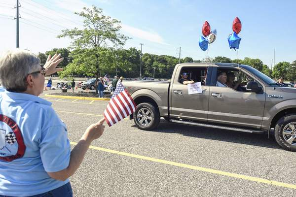 Michelle Davies   The Journal Gazette Spectators wave to participants in Saturday morning's Drive-Thru Salute to All Veterans in the parking lot at Memorial Coliseum. The salute was conducted by Honor Flight Northeast Indiana.