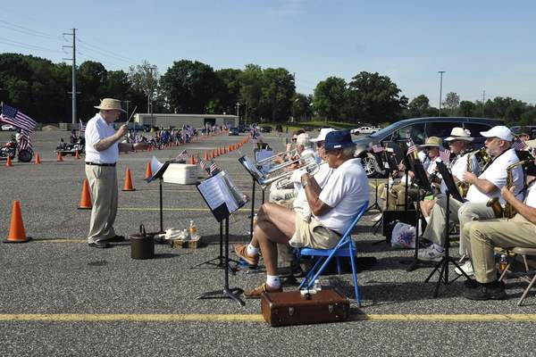 """Michelle Davies   The Journal Gazette Under the direction of Eli Arnold, members of the American Legion Band of Fort Wayne, played at Saturday's """"A Drive Thru Salute to All Veterans"""" in the parking lot of the Allen County War Memorial Coliseum. The drive thru was presented by Honor Flight Northeast Indiana (HFNEI)."""
