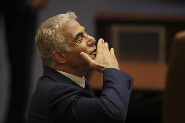 Israeli politician Yair Lapid of the Yesh Atid party sends greetings during a Knesset session in Jerusalem Sunday, June 13, 2021. (AP Photo/Ariel Schali22
