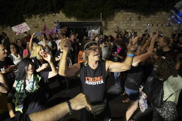Israeli protesters dance and cheer during a demonstration against Israeli Prime Minister Benjamin Netanyahu outside his official residence in Jerusalem, Saturday, June 12, 2021. (AP Photo/Ariel Schalit)