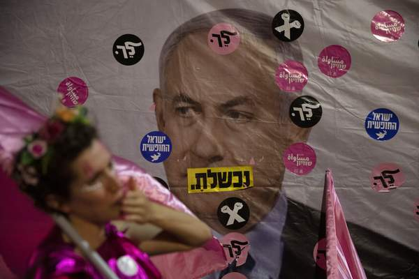 An Israeli protester wears pink during a demonstration against Israeli Prime Minister Benjamin Netanyahu outside his official residence in Jerusalem, Saturday, June 12, 2021. (AP Photo/Ariel Schalit)