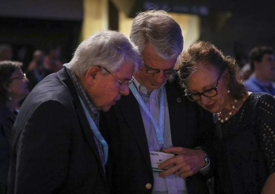 FILE - In this Wednesday, June 12, 2019 file photo, from left, Dick Lane, Al Jackson and his wife, Kem Jackson, pray on the second day of the Southern Baptist Convention's annual meeting in Birmingham, Ala. ( Jon Shapley/Houston Chronicle via AP, File)