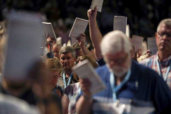 FILE - In this Wednesday, June 12, 2019 file photo, Bill Golden, and thousands of others, hold up copies of a training handbook related to sexual abuse within Southern Baptist churches during a speech by SBC President J. D. Greear on the second day of the SBC's annual meeting in Birmingham, Ala. ( Jon Shapley/Houston Chronicle via AP, File)