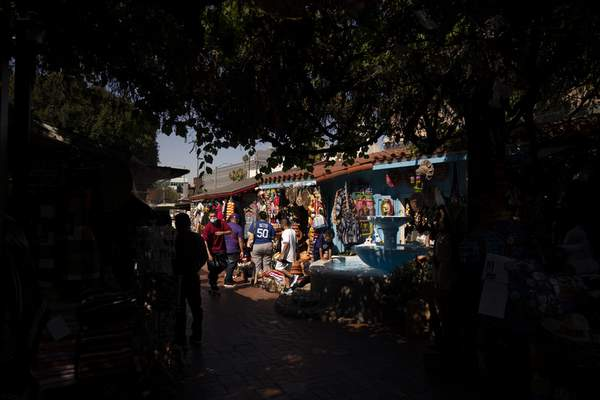 People shop on Olvera Street in Los Angeles, Friday, June 4, 2021. Olvera Street has long been a thriving tourist destination and a symbol of the state's early ties to Mexico. (AP Photo/Jae C. Hong)