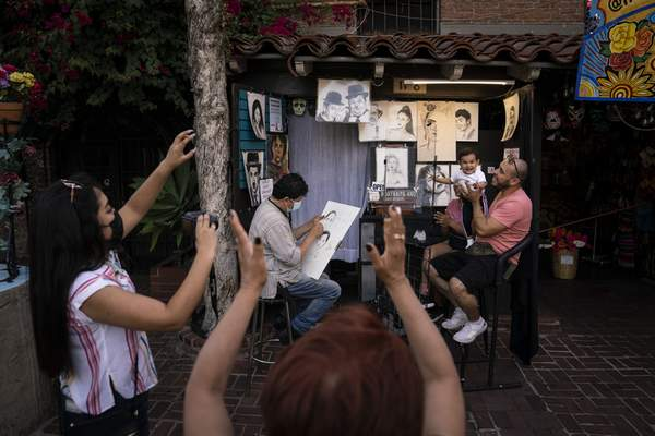 Relatives of 1-year-old Janelly Cerda, visiting from Tijuana, Mexico, gesture to make the toddler smile for photos as caricaturist Hernan Davila sketches the family on Olvera Street in Los Angeles, Tuesday, June 8, 2021. (AP Photo/Jae C. Hong)
