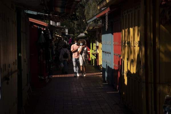 Alexia Thorpe and her boyfriend, Bennett Olupo are lit by afternoon sunlight as they stroll past stalls lining along Olvera Street in Los Angeles, Friday, June 4, 2021. (AP Photo/Jae C. Hong)