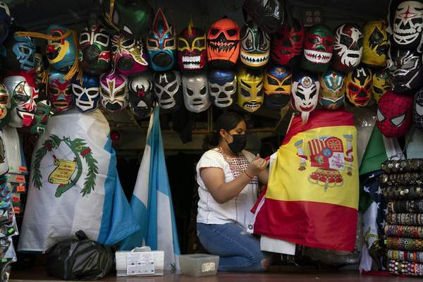 Clerk Wendy Ramirez uses a Spanish flag to wrap souvenirs while preparing to close the store for the day on Olvera Street in Los Angeles, Tuesday, June 8, 2021. (AP Photo/Jae C. Hong)