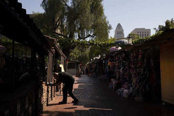 Peter Alamillo, one of managers at El Paseo Inn Mexican restaurant on Olvera Street, pulls down a blind for customers in the patio area of the restaurant in Los Angeles, Friday, June 4, 2021. (AP Photo/Jae C. Hong)